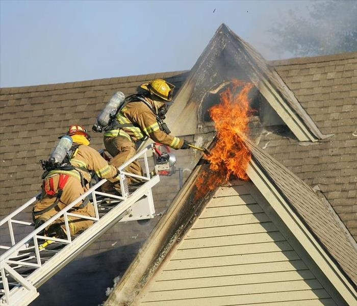 Firemen on ladder extinguishing a second story fire
